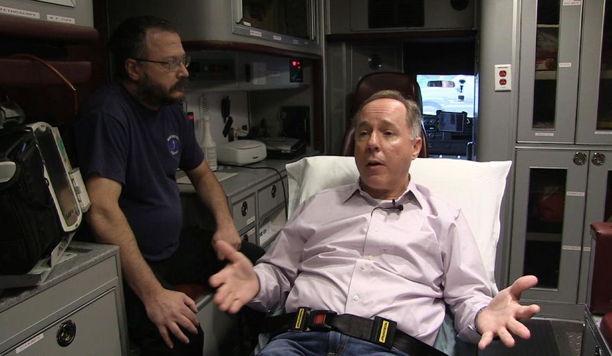 This Sept. 23, 2016 frame grab from video provided by the office of Wisconsin state Assembly Speaker Robin Vos shows Vos, right, and his cousin Mike Vos, a volunteer with the Burlington Rescue Squad, sitting in the back of an ambulance in Burlington, Wis. The video was released Monday, Dec. 5, 2016, a day before an Assembly committee is to hold a public hearing on how to fix the state's $1 billion transportation budget shortfall. Vos is among a group of Assembly Republican leaders arguing that increasing the gas tax should be considered along with other options. (Office of Wisconsin state Assembly Speaker Robin Vos via AP)