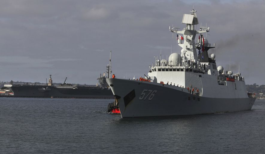 The Chinese Navy frigate Daqing 576 approaches the waterfront in San Diego, Calif., with a U.S. aircraft carrier on the North Island base in the background, Tuesday, Dec. 6, 2016. Three People's Liberation Army (Navy) ships are visiting San Diego as part of a routine port visit, from Dec. 6-9. (Peggy Peattie/The San Diego Union-Tribune via AP)