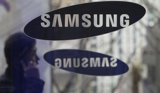 In this Dec. 12, 2013 file photo, a man passes by the Samsung Electronics Co. logos at its headquarters in Seoul, South Korea. A unanimous Supreme Court on Tuesday, Dec. 6, 2016, sided with smartphone maker Samsung in its high-profile patent dispute with Apple over design of the iPhone. The justices said Samsung may not be required to pay all the profits it earned from 11 phone models because the features at issue are only a tiny part of the devices.  (AP Photo/Ahn Young-joon, File) **FILE**