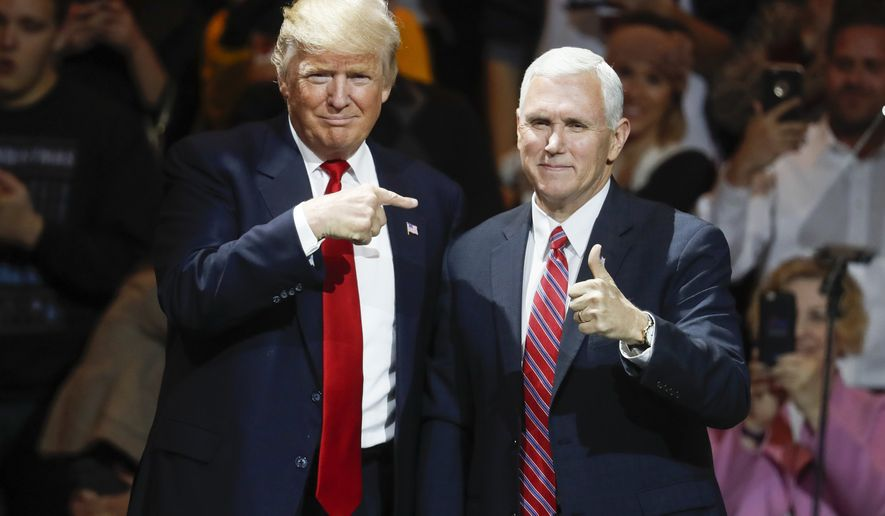 President-elect Donald Trump, left, and Vice President-elect Mike Pence acknowledge the crowd during the first stop of his post-election tour, in Cincinnati, Dec. 1, 2016. The Heritage Foundation says Pence will deliver a speech Tuesday night, Dec. 6, 2016, to a conservative group at Trumps new hotel in Washington, about areas of focus for the Trump administration in the first 200 days. (AP Photo/John Minchillo, File) ** FILE **