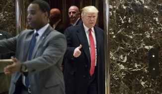 President-elect Donald Trump gestures as he arrives in the lobby of Trump Tower in New York, Tuesday, Dec. 6, 2016, to speak to members of the media. (AP Photo/Andrew Harnik)