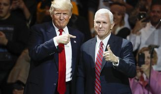 In this Thursday, Dec. 1, 2016, file photo, President-elect Donald Trump, left, and Vice President-elect Mike Pence acknowledge the crowd during the first stop of his post-election tour, in Cincinnati. The Heritage Foundation says Pence will deliver a speech Tuesday night, Dec. 6, 2016, to a conservative group at Trumps new hotel in Washington, about areas of focus for the Trump administration in the first 200 days. (AP Photo/John Minchillo, File)