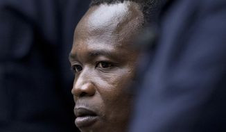 Dominic Ongwen, a senior commander in the Lord's Resistance Army, whose fugitive leader Kony is one of the world's most-wanted war crimes suspects, is flanked by two security guards as he sits in the court room of the International Court in The Hague, Netherlands, Tuesday, Dec. 6, 2016. (AP Photo/Peter Dejong, Pool)