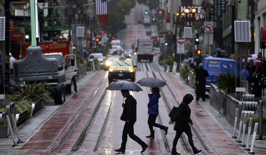 FILE - In this  Oct. 14, 2016, file photo pedestrians carry umbrellas as they cross Powell Street and cable car tracks in San Francisco. State officials said Tuesday, Dec. 6 that Californians did a good job of saving water in October, a month of heavy rain falling amid ongoing drought. State regulators say cities improved water conservation by nearly 20 percent compared to 2013, before the declaration of a drought emergency. (Paul Chinn /San Francisco Chronicle via AP)