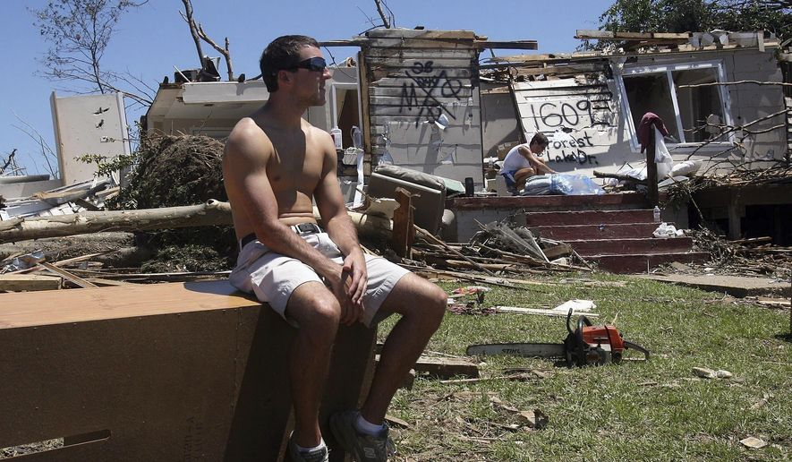 FILE- In this April 29, 2011, file photo, Huston Walters, a sophomore at the University of Alabama from Navarre, Fla., takes a break from cleaning up at his home in the Forest Lake neighborhood after a tornado struck the area. For college administrators, extreme weather is yet another hazard to prepare and practice for on a list that includes infectious disease outbreaks, active shooters and technological outages. (Michelle Lepianka Carter/The Tuscaloosa News via AP, File)