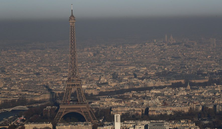 The Eiffel Tower is seen from a hot air balloon as Paris suffers a pollution spike, Monday Dec. 5, 2016. Paris authorities have adopted measures to limit traffic speed after high levels of pollution in the French capital. (AP Photo/Christophe Ena)