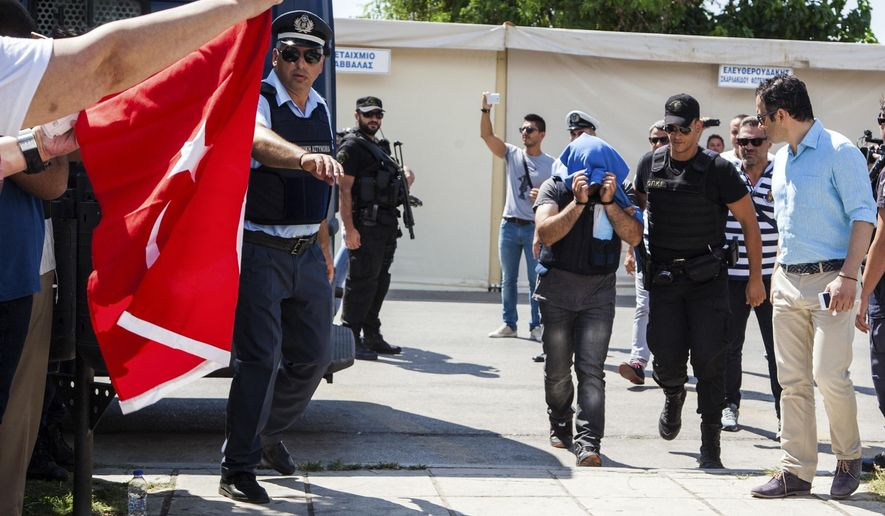 FILE - In this Thursday, July 21, 2016 file photo, a Turkish military officer is transferred to a court hall in the city of Alexandroupolis, northern Greece. A Greek court in Athens, on Tuesday, Dec. 6, 2016 has ruled to extradite three of eight Turkish servicemen who fled to Greece after a failed July 15 military coup, a day after rejecting Turkey's extradition request for another three of the group. (Antonis Pasvantis/InTime News via AP, file)