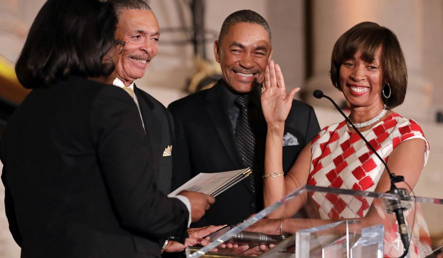 Catherine Pugh, right, smiles as she takes the oath of office to become Baltimore's 50th mayor during her inauguration ceremony inside the War Memorial Building in Baltimore, Tuesday, Dec. 6, 2016. Standing with Pugh are Judge Shirley Watts of the Maryland Court of Appeals, from left, and Pugh's brothers, James and Ardell Crump. (AP Photo/Patrick Semansky)