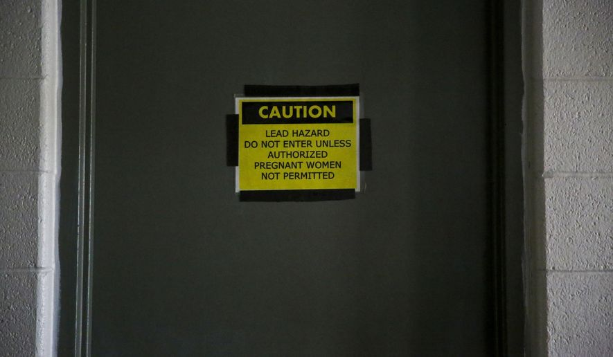 In this Friday, Dec. 2, 2016 photo a lead hazard sign is posted on the boiler room door at the Grand Valley Armory in Wyoming, Mich. Documents say dangerous lead levels went unchecked at Michigan National Guard armories that were polluted due to their use as indoor firing ranges. Testing in 2014 and 2015 showed lead dust levels above recommended levels, including the Grand Valley Armory.  (Chelsea Purgahn  /Kalamazoo Gazette-MLive Media Group via AP)