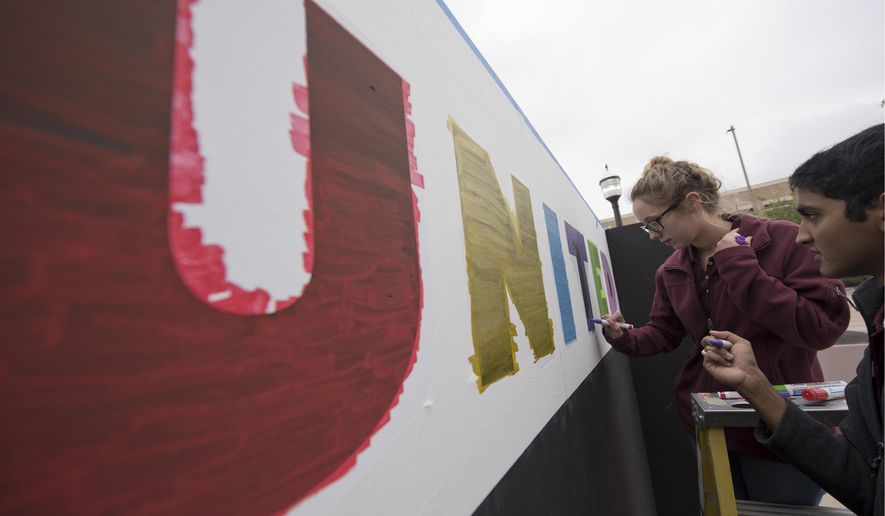 """Texas A&M students Brendan D'Souza, right, and Sarah Minton paint a stencil on the """"Expression Wall"""" put up in front of Kyle Field, Tuesday, Dec. 6, 2016, in College Station, Texas, before the university's """"Aggies United"""" event.  The university is preparing to hold the event highlighting diversity and unity at the school, at the same time as Richard Spencer, who leads a movement that mixes racism, white nationalism and populism, is set to speak at the College Station campus. (Timothy Hurst/College Station Eagle via AP)"""