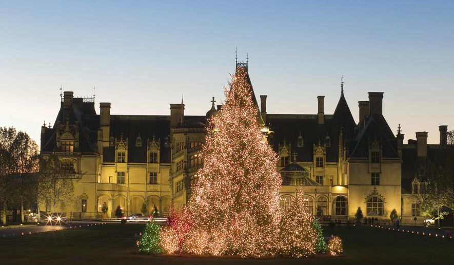 This Nov. 4, 2016 photo shows a massive Christmas tree covered in lights outside The Biltmore House in Asheville, N.C. Lonely Planet has named Asheville the No. 1 destination on its 10 best in the U.S. list for 2017.(LeeAnn Donnelly/The Biltmore via AP)