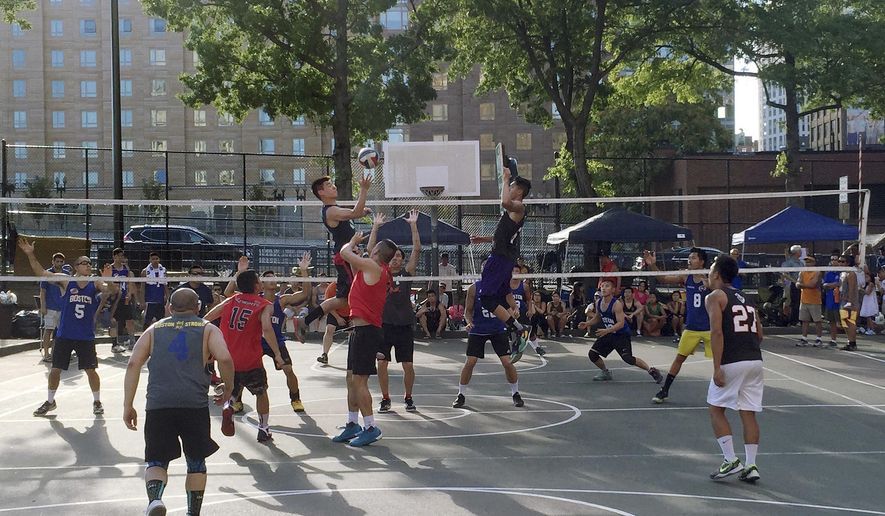 In this Aug. 14, 2016 photo provided by Virginia Tow, players of the Boston Knight A volleyball team, front, go up for a spike against the Boston Hurricanes Black team during the August Moon Festival at Reggie Wong Park in the Chinatown neighborhood in Boston. The fate of a modest asphalt court where Chinese immigrants developed a unique style of volleyball is uncertain. The state of Massachusetts is seeking proposals to develop a prime slice of real estate near Boston's Chinatown that was a nursery for nine-man volleyball. (Virginia Tow via AP)