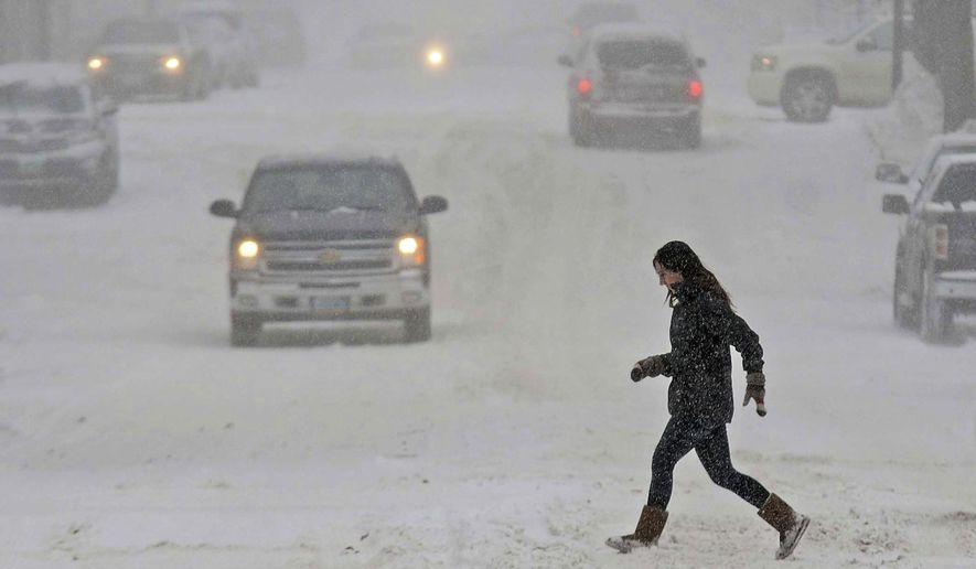 A woman tries to walk across a street in Bismarck, N.D., Monday, Dec. 5, 2016. Strong winds and blowing snow are making travel hazardous in much of northwestern and south-central North Dakota. (Tom Stromme/The Bismarck Tribune via AP)