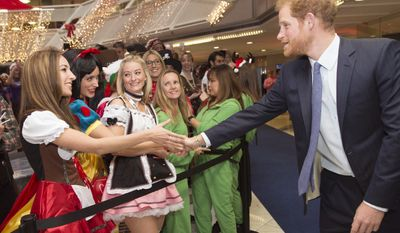 Britain's Prince Harry, right, attends an ICAP Charity Trading Day in support of Sentebale - a charity supporting orphans and vulnerable children, in London, Wednesday, Dec. 7, 2016.  (Geoff Pugh/Pool Photo via AP)