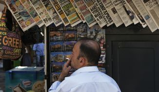 FILE - This is a Sunday, July 12, 2015 file photo of a man as he smokes a cigarette as he looks at daily newspapers displayed at a kiosk in central Athens. Nearly two-thirds of Greeks are inhaling someone else's tobacco smoke on a daily basis, making Greece the worst nation in the European Union in exposing its people to the health risks of passive smoking. The European Union's statistical office Eurostat said Wednesday Dec. 7, 2016 that 64.2 percent of Greeks suffered daily exposure to tobacco smoke indoors.  (AP Photo/Petros Karadjias, File)