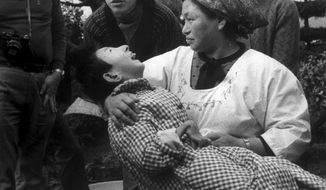 "FILE - In this 1973 photo, a woman holds a victim of ""Minamata Disease"", or mercury poisoning, in Minamata, Japan. The girl has a malformed hand, like many victims of the disease who suffer from physical deformites among other symptoms.  The Tokyo District Court has rejected a civil lawsuit demanding that tests into food toxicity and illnesses required by law be carried out for ""Minamata disease"" poisoning. Doctor Toshihide Tsuda, who sued, said Wednesday, Dec. 7, 2016,  he would appeal the court's decision. (AP Photo, File)"