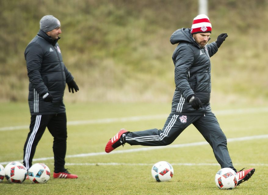 Toronto FC head coach Greg Vanney, right, kicks the ball during practice in Toronto on Wednesday, Dec. 7, 2016. Toronto FC will play the Seattle Sounders in the MLS Cup, the soccer leagues championship, on Saturday, Dec. 10, in Toronto. (Nathan Denette/The Canadian Press via AP)