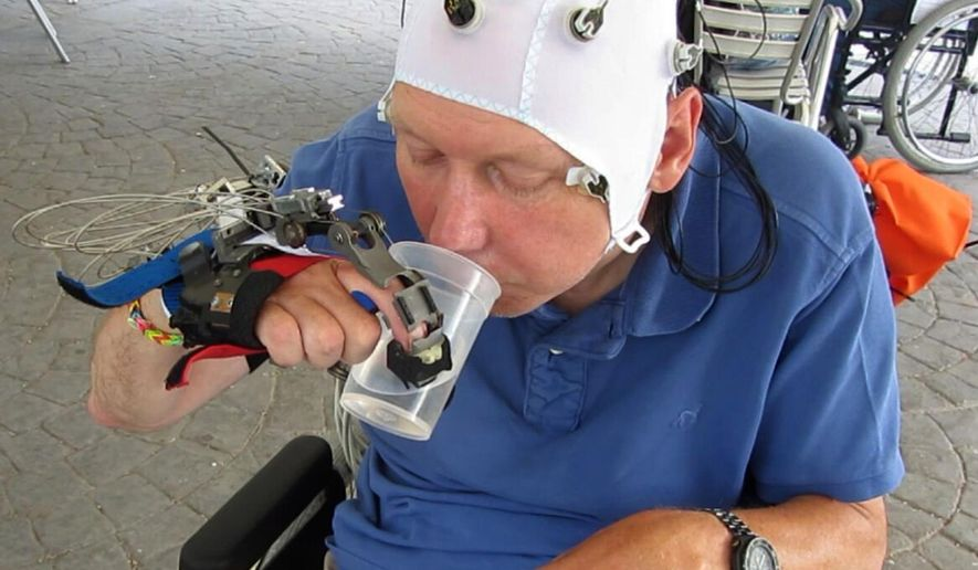 In this undated grab taken from video, a patient uses a robotic hand to drink from a cup, in Badalona, Spain. Scientists have developed a mind-controlled robotic hand that allows people with certain types of spinal injuries to perform everyday tasks such as using a fork or drinking from a cup. (Mario Cortese video via AP)