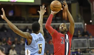 Washington Wizards guard John Wall (2) takes a shot against Denver Nuggets guard Will Barton (5) during the second half of an NBA basketball game, Thursday, Dec. 8, 2016, in Washington. The Wizards won 92-85. (AP Photo/Nick Wass)