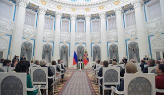 Russian President Vladimir Putin, background center, speaks during a  government awards'  presentation ceremony in the Kremlin, in Moscow, Russia, Thursday, Dec. 8, 2016. (Alexei Druzhinin/Sputnik, Kremlin Pool Photo via AP)