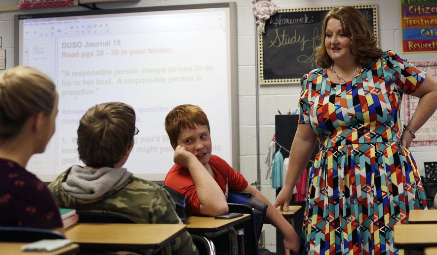 ADVANCE FOR USE SUNDAY, DEC. 11, 2016 AND THEREAFTER - In this Nov. 17, 2016 photo, Melanie Swann, right, listens as seventh-grader Noah Ward,  center, talks with classmates during her Developing an Understanding of Self and Others class at West Frankfort Central Junior High School in West Frankfort, Ill. Swann designed the class five years ago to help seventh and eighth-graders develop an understanding of how to deal with people different than themselves. Swann said the last election cycle has often been a topic of discussion. (Issac Smith /The Southern, via AP)
