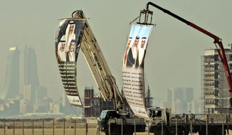 FILE- In this Jan. 6, 2010 file photo, construction cranes display huge banners with poetry welcoming Bahrain's leaders -- King Hamed bin Isa Al Khalifa, Prime Minister Prince Khalifa bin Salman Al Khalifa and Crown Prince Salman bin Hamed Al Khalifa, in Muharraq, Bahrain. In a slickly produced Islamic State group propaganda video, that surfaced as a Gulf Cooperation Council conference attended by British Prime Minister Theresa May ended on Wednesday, Dec. 7, 2016, IS called on its followers to launch attacks in Bahrain, including those targeting American military personnel stationed on the tiny island ahead of a visit by the U.S. defense secretary. (AP Photo/Hasan Jamali, File)