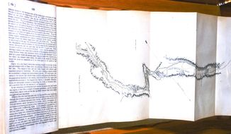 This Dec. 1, 2016 photo taken at the National Historic Oregon Trail Interpretative Center in Baker City, shows the fold out map inside the John C. Fremont book displayed there. Through a partnership between the Library of Congress and the office of Sen. Ron Wyden, D-Ore., the 170-year-old, seven-section topographical map of the Oregon Trail that is bound into the book, has been secured for display at the Center. (S. John Collins  /Baker City Herald via AP)