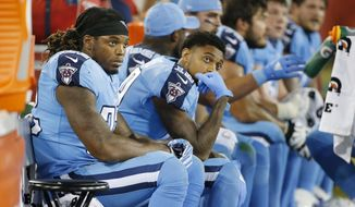 FILE - In this Oct. 27, 2016, file photo, Tennessee Titans running back Derrick Henry, left, sits next to wide receiver Tajae Sharpe (19) on the sideline in the first half of an NFL football game against the Jacksonville Jaguars, in Nashville, Tenn. A year after winning the Heisman Trophy, rookie running back Derrick Henry is practicing patience playing with the Tennessee Titans where he is backing up the NFL's second-best rusher in DeMarco Murray. (AP Photo/Weston Kenney, File)
