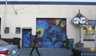 In this photo taken Wednesday, Dec. 7, 2016, a woman walks past a mural painted on the exterior of an underground artist collective warehouse known as The Death Trap in Oakland, Calif. Oakland and its abandoned warehouses have long been hospitable to an underground art scene that helped put this gritty city on the world art map. But now the art and music underground is panicking, and bracing for a crackdown. They're fearful because of safety issues exposed by the fire that killed 36 people at a warehouse dance party. (AP Photo/Jocelyn Gecker)