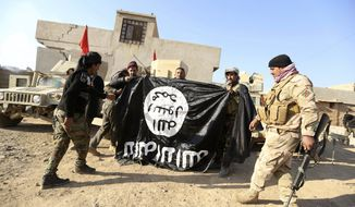 In this Nov. 29, 2016 file photo, Iraqi Army soldiers celebrate as they hold a flag of the Islamic State group they captured during a military operation to regain control of a village outside Mosul, Iraq. (AP Photo/Hadi Mizban, File)