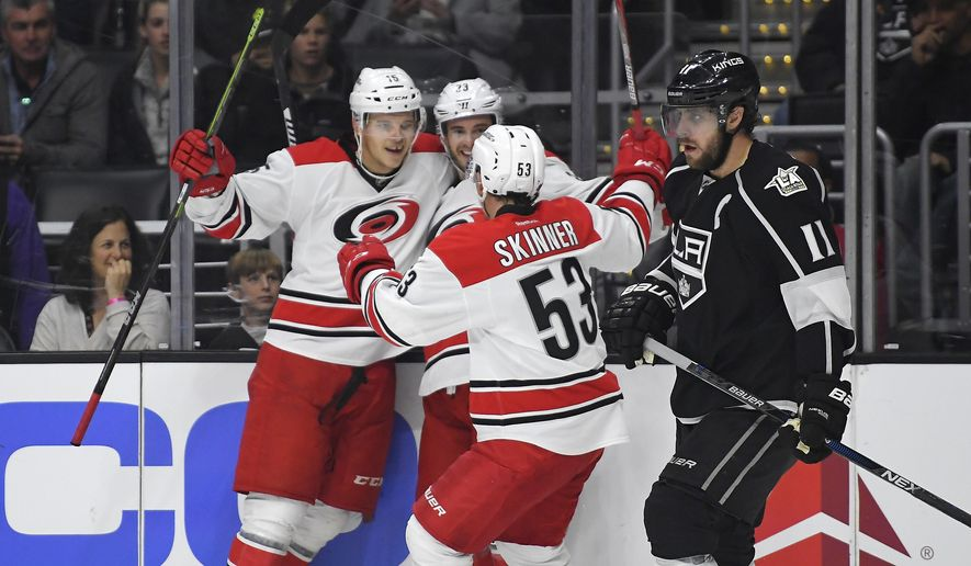 Carolina Hurricanes center Derek Ryan, second from left, celebrates his goal with center Andrej Nestrasil, left, of the Czech Republic, and left wing Jeff Skinner, second from right, as Los Angeles Kings center Anze Kopitar, of Slovenia, skates by during the first half of an NHL hockey game, Thursday, Dec. 8, 2016, in Los Angeles. (AP Photo/Mark J. Terrill)