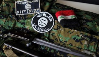 In this Dec. 2, 2016 photo, a pair of Daesh, or ISIS, patches, a wrist band featuring Syrian government markings and a bayonet collected from the battlefield in Syria are arranged atop on of Freeman Stevenson's YPG camouflage uniforms arranged for a photograph in Saratoga Springs, Utah. Stevenson volunteered for combat alongside the Kurdish militia and said he wanted to fight the Islamic State. (Spenser Heaps/The Deseret News via AP)