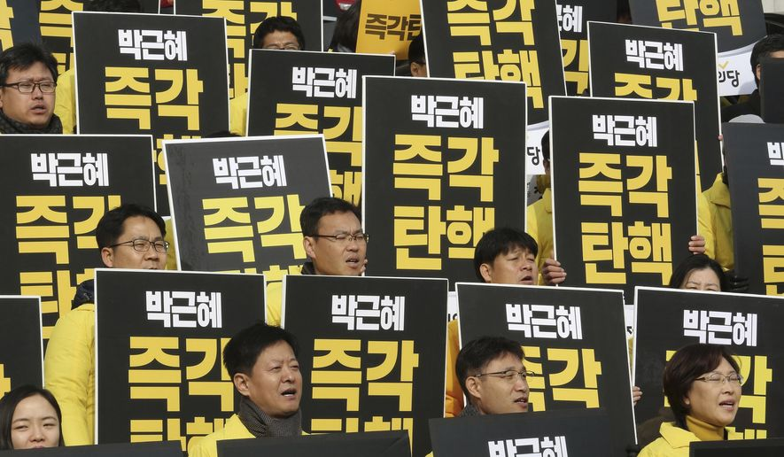 """Lawmakers and members of opposition Justice Party shout slogans during a rally demanding the impeachment of South Korean President Park Geun-hye at the National Assembly in Seoul, South Korea, Thursday, Dec. 8, 2016. Park, who faces the political fight of her life as lawmakers attempt to force her from office over prosecution claims that she helped a confidante extort money and favors from companies and manipulate state affairs. The signs read: """"Impeach Park Geun-hye immediately."""" (AP Photo/Ahn Young-joon)"""