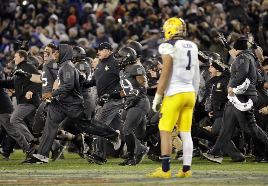 Navy safety Alohi Gilman (1) watches as Army players and coaches run onto the field after winning the Army-Navy NCAA college football game in Baltimore, Saturday, Dec. 10, 2016. Army won 21-17. (AP Photo/Patrick Semansky)