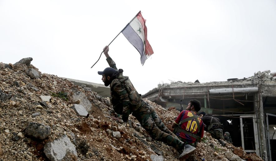 In this Monday, Dec. 5, 2016 file photo, a Syrian army soldier places a Syrian national flag during a battle with rebel fighters at the Ramouseh front line, east of Aleppo, Syria. (AP Photo/Hassan Ammar, File)