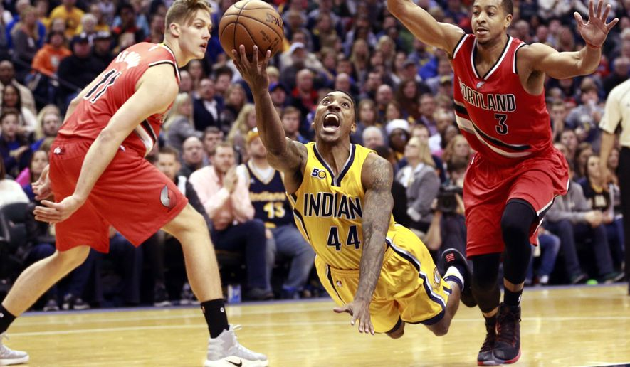 Indiana Pacers guard Jeff Teague (44) shoots while falling between Portland Trail Blazers forward Meyers Leonard, left, and guard C.J. McCollum (3) in the second half of an NBA basketball game, Saturday, Dec. 10, 2016, in Indianapolis. (AP Photo/R Brent Smith)