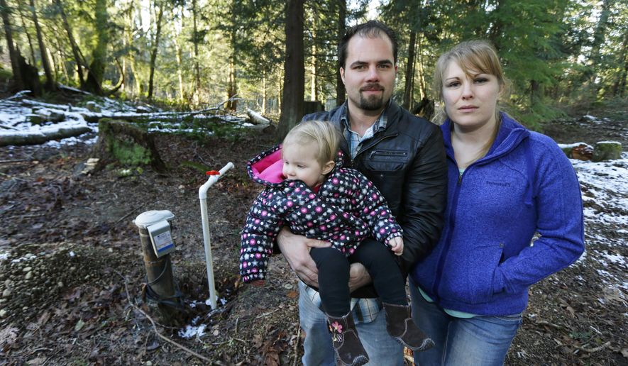 In this Dec. 6, 2016 photo, Bud Breakey and his wife Deborah pose for a photo with their daughter Kaylin, 15 mos., by the well they paid to drill on property they own near Bellingham, Wash. The couple hopes to live on the land soon and build a house, but in October, the Washington state Supreme Court ruled that Whatcom County failed to protect water resources by allowing new wells to reduce flow in streams for fish and other uses, leaving landowners like the Breakeys in limbo. Now counties have to figure out how to ensure water is legally available before granting new building permits. (AP Photo/Ted S. Warren)