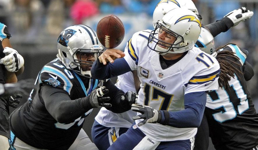 San Diego Chargers' Philip Rivers (17) fumbles the ball aster being hit by Carolina Panthers' Kawann Short (99) in the first half of an NFL football game in Charlotte, N.C., Sunday, Dec. 11, 2016. (AP Photo/Mike McCarn)