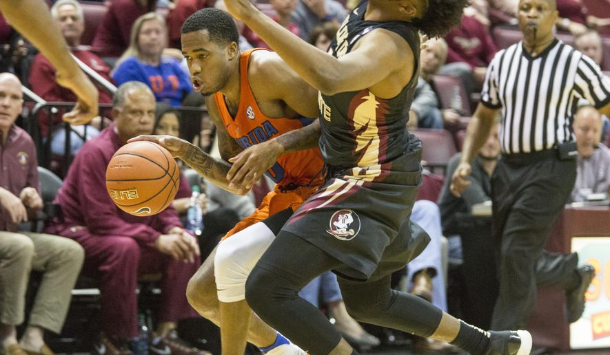 Florida guard Kasey Hill drives against Florida State guard Kevaughn Allen in the first half of an NCAA college basketball game in Tallahassee, Fla., Sunday, Dec. 11, 2016. (AP Photo/Mark Wallheiser)