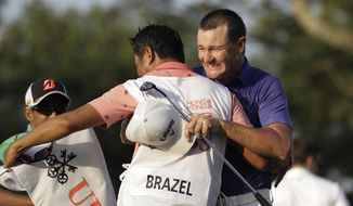 Australia's Sam Brazel, right, celebrates with his caddie on the 18th hole after winning the Hong Kong Open golf tournament in Hong Kong, Sunday, Dec. 11, 2016. Brazel birdied the 18th hole to narrowly edge Rafa Cabrera Bello of Spain to capture the Hong Kong Open on Sunday, his first title on the European Tour. (AP Photo/Kin Cheung)