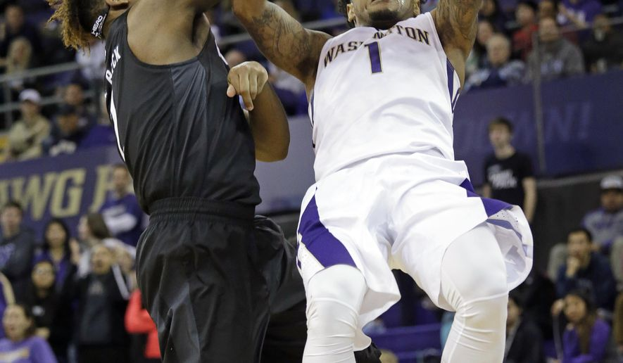 Nevada's Leland King II, left, knocks away the ball as Washington's David Crisp tries to shoot in the first half of an NCAA college basketball game Sunday, Dec. 11, 2016, in Seattle. (AP Photo/Elaine Thompson)