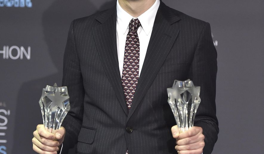 """Damien Chazelle poses in the press room with the awards for best picture and best director for """"La La Land"""" at the 22nd annual Critics' Choice Awards at the Barker Hangar on Sunday, Dec. 11, 2016, in Santa Monica, Calif. (Photo by Jordan Strauss/Invision/AP)"""