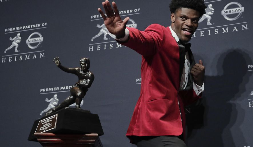 FILE - In this Dec. 10, 2016, file photo, Louisville's Lamar Jackson poses with the Heisman Trophy after winning the Heisman Trophy award in New York. Jackson was selected to the 2016 AP All-America college football team, Monday, Dec. 12, 2016. (AP Photo/Julie Jacobson, File)