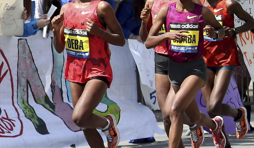 FILE - In this Monday, April 21, 2014, file photo Buzunesh Deba, left, of Ethiopia, runs in a group of elite female participants past Wellesley College during the 118th Boston Marathon in Wellesley, Mass. Deba was named the 2014 Boston Marathon winner Monday with a time of 2:19:59 following the disqualification of Rita Jeptoo for doping. Deba now becomes the rightful 2014 winner and current course record-holder. (AP Photo/Mary Schwalm, File)