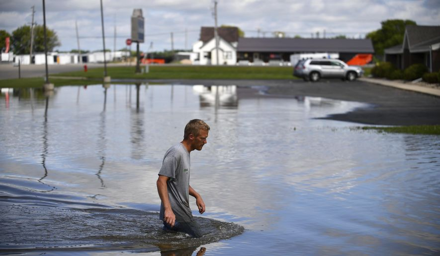 """FILE - In this Aug. 11, 2016 file photo, Chad Koosman, of Willmar, Minn., wades through flood water behind one of his apartment properties. As global temperatures warm, Minnesotans need to prepare for increases in catastrophic """"mega-rains"""" and a greater spread of tick-borne illnesses such as Lyme disease, according to a draft environmental report card for the state.The report card comes from the Environmental Quality Board, a coordinating body for state government agencies on environmental issues. (Aaron Lavinsky/Star Tribune via AP File)"""