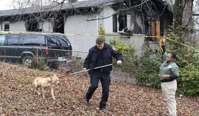 Springfield Police officer Jay Pattie and Zoraida Luna of Animal Control remove a dog from the property of fatal house fire where multliple children died Monday, Dec. 12, 2016, in Springfield, Tenn.  (Mark Zalesky/The Tennessean via AP)