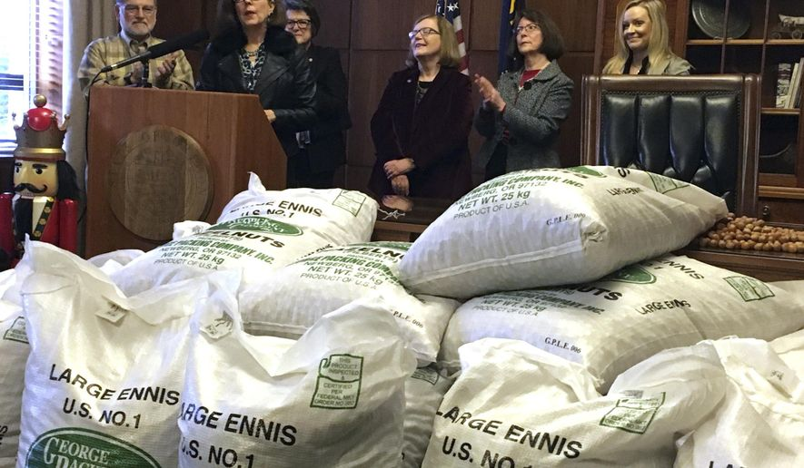 Oregon Gov. Kate Brown, at podium, celebrates Oregon's first year of an automatic voter registration program on Monday, Dec. 12, 2016 with a news conference, where she said that in the November election, over 97,000 ballots were cast by new voters registered by the so-called motor voter program. Hazelnuts contained in the bags in the foreground represent the 270,000 Oregonians who were registered to vote by the program. (AP Photo/Andrew Selsky)