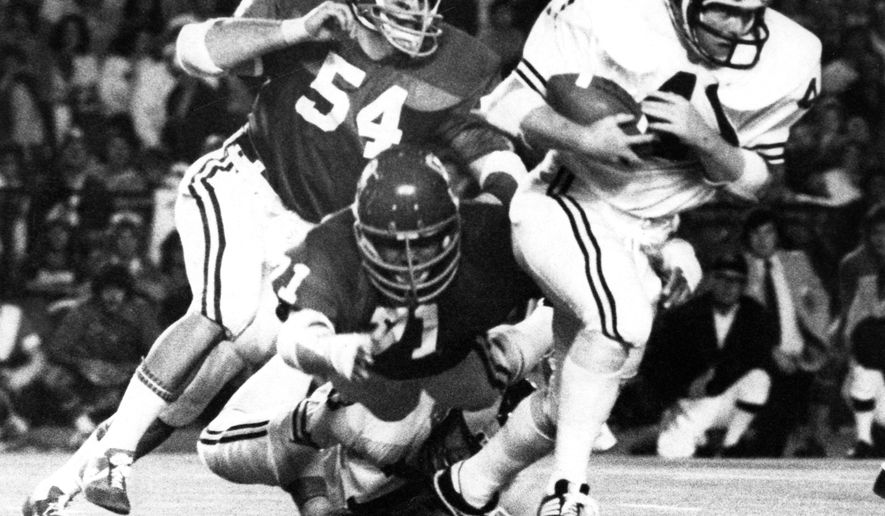 "In this Jan. 1, 1976, photo, Oklahoma NCAA college football defensive end Jimbo Elrod (54) pursues Michigan fullback Rob Lytle (41) during the Orange Bowl game in Miami. The Oklahoma Highway Patrol says former Oklahoma All-American James ""Jimbo"" Elrod, who played on the Sooners' 1974 and 1975 national championship teams, has died in a car wreck. He was 62. The highway patrol says the single-vehicle crash happened at about 3:45 a.m. Monday, Dec. 12, 2016, on Interstate 44 near Chandler, about 60 miles southwest of Tulsa. (Jim Argo/The Oklahoman via AP)"
