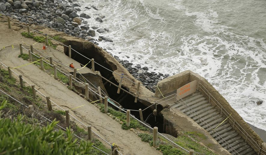A sinkhole on the side of a cliff above the ocean is viewed Monday, Dec. 12, 2016, in Pacifica, Calif. Large waves, known as king tides, could have caused a sinkhole that emerged over the weekend on the coast south of San Francisco. (AP Photo/Eric Risberg)