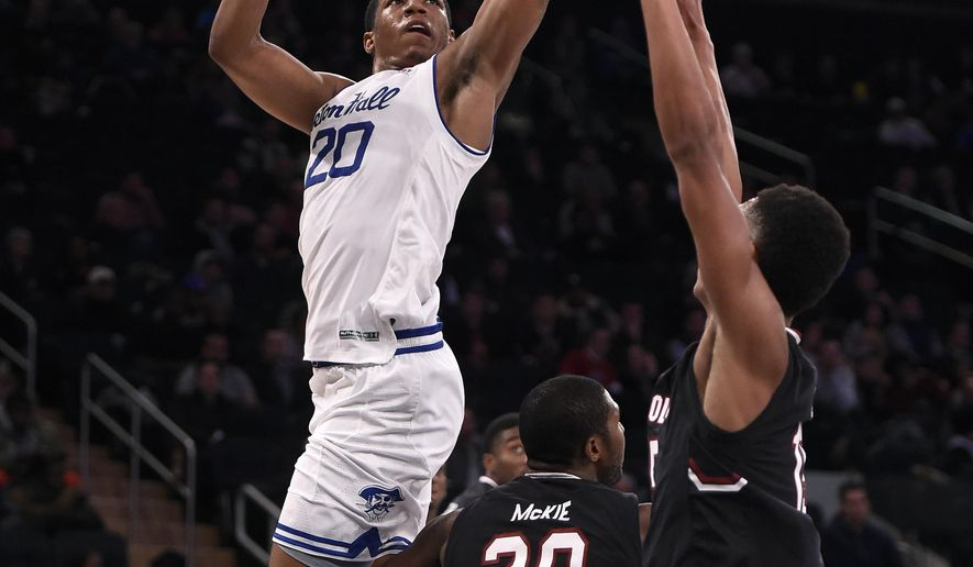 Seton Hall forward Desi Rodriguez (20) shoots over South Carolina guard Justin McKie (20) and guard PJ Dozier (15) )in the first half of an NCAA college basketball game, Monday, Dec. 12, 2016, in New York. (AP Photo/Kathy Kmonicek)